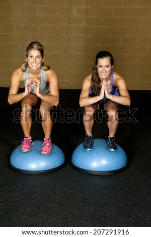 Two athletic female trainers do a squat on a bosu ball in a gym