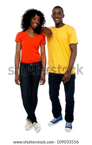 Two attractive african friends posing in style as guy rests his hands over his girlfriends shoulders