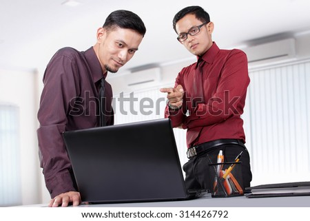 Two attractive Asian office workers discussing something on a laptop at their office workplace - stock photo