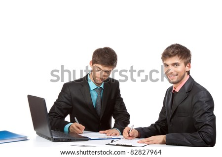 Two attractive business people in elegant suits sitting at desk working in team together, discussing the problem, working on laptop, clipboard with papers, document, Isolated over white background
