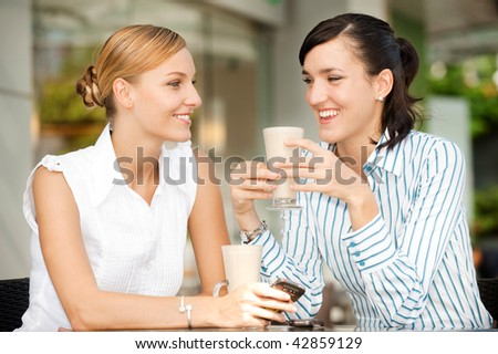 Two attractive businesswomen chatting over coffee