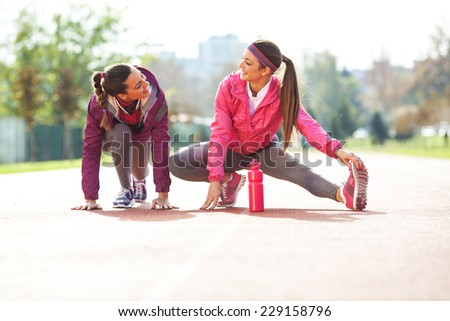 Two attractive female at the race track.Stretching. - stock photo
