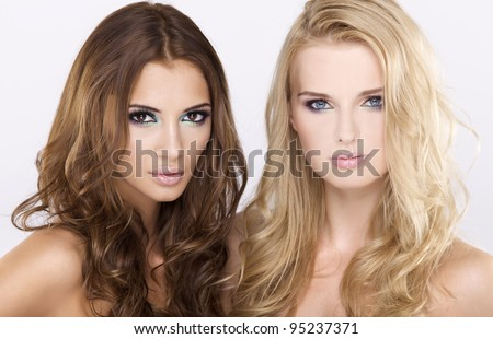 Two attractive girl friends - blond and brunette on white background - stock photo