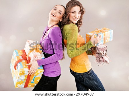 Two attractive girls holding gifts