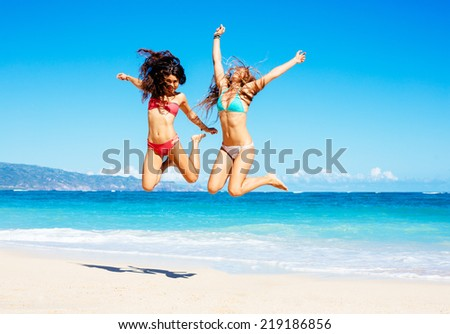 Two Attractive Girls in Bikinis Jumping on the Beach. Best Friends Having Fun, Summer Lifestyle. - stock photo