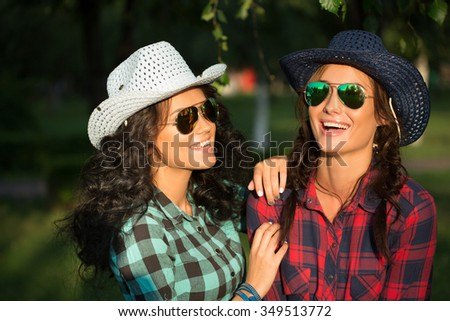 Two attractive girls in cowboy hats and sunglasses walking park. happily laughing - stock photo
