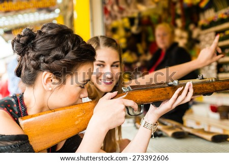 Two attractive girls playing shooting games at German funfair Oktoberfest. Both wearing traditional Dirndl dresses, the one in front having an Asian touch - stock photo