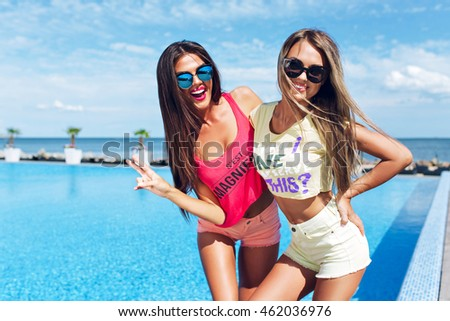 Two attractive girls with long hair are posing near pool on the sun. Brunette girl wears short pink shorts and T-shirt, blond wears yellow shorts and T-shirt. They are smiling to the camera.