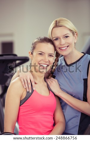 Two attractive happy healthy fit young women posing arm in arm at the gym smiling at the camera in a health and fitness concept - stock photo