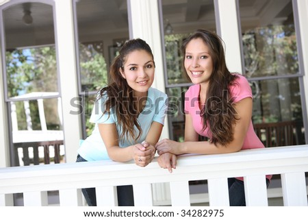 Two attractive hispanic sisters having fun at home on the porch - stock photo