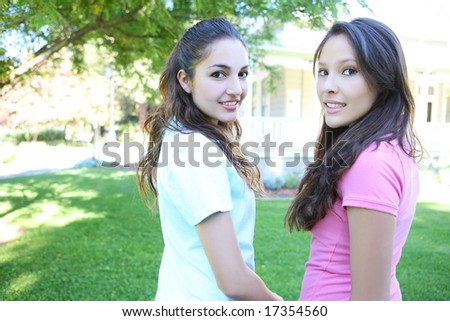 Two attractive hispanic sisters smiling at home - stock photo