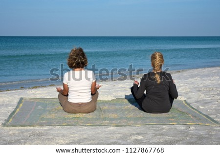 Two Attractive Mature Women doing Yoga at Sunrise on the Beach