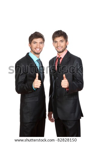 Two attractive positive smile young business people standing and holding hands with thumbs up gesture, dressed in suit, shirt, tie. Concept Success, Approval, Good Work, isolated over white background - stock photo