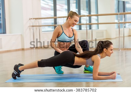 Two attractive sport girls smiling while working out and doing plank exercise in fitness class - stock photo