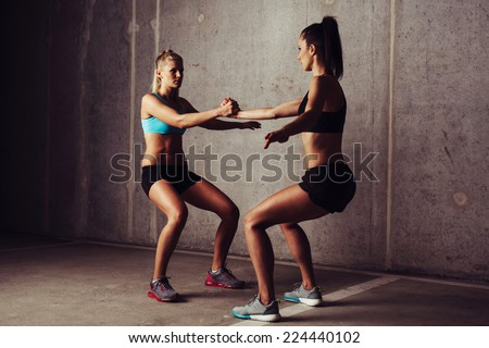 Two attractive sportswomen stretching against a concrete background - stock photo