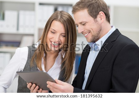 Two attractive stylish young co-workers smiling at information on a tablet held by the man as they stand together in the office - stock photo