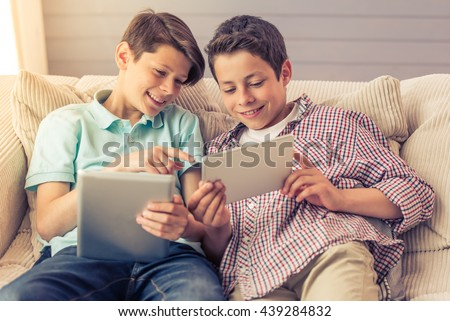 Two attractive teenage boys are using tablets, talking and smiling while sitting on the couch at home - stock photo
