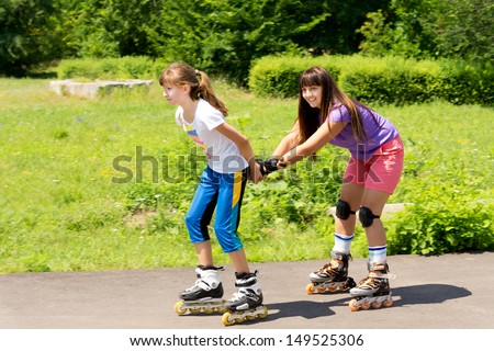 Two attractive teenaged female friends roller skating with the one pulling the other along behind her in a lush green rural park - stock photo