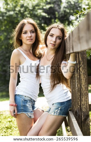 Two attractive twin sisters in a park in summer