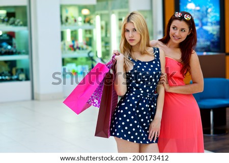 two attractive woman friends with shopping bags in shopping mall
