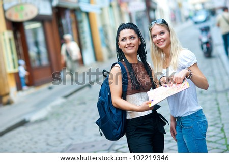 two attractive woman tourists looking at the map in the city - stock photo