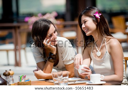 Two attractive women at breakfast on vacation - stock photo