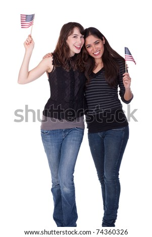 Two attractive women, casually dressed, holding small American flags.