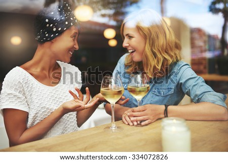 Two attractive women enjoying a glass of white wine together in a pub sitting at a table laughing and chatting with reflections on the window glass, young multiracial couple - stock photo