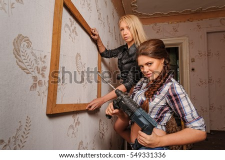 Two attractive women hang up a frame for picture. Home improvement theme