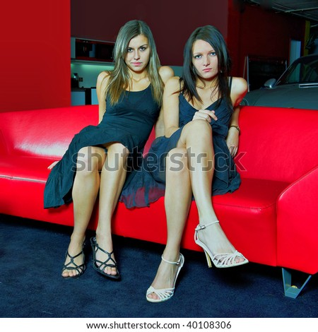 Two attractive women in black dresses, heels and with long hairs on red sofa