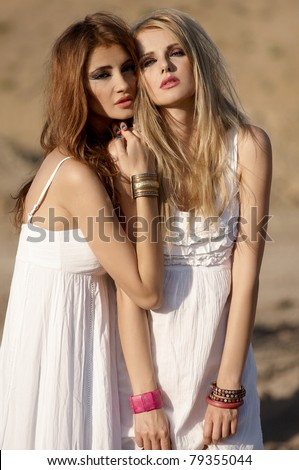 two attractive women in white dresses standing in the desert