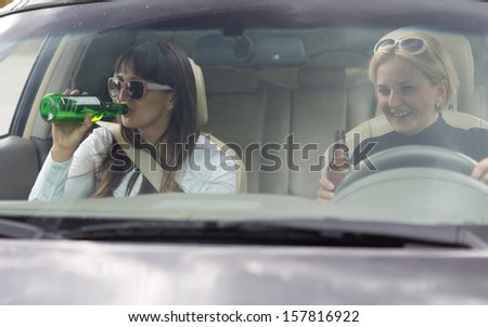 Two attractive women partying and drinking while driving along in a car, view through the front windscreen - stock photo
