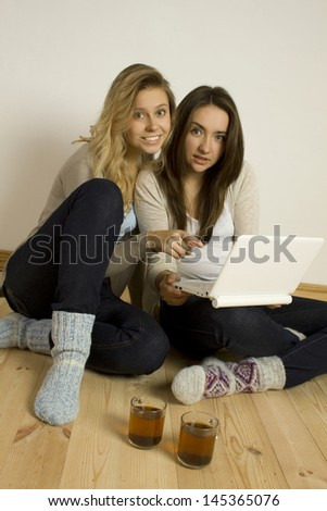 Two attractive women sitting at home on the floor with a laptop