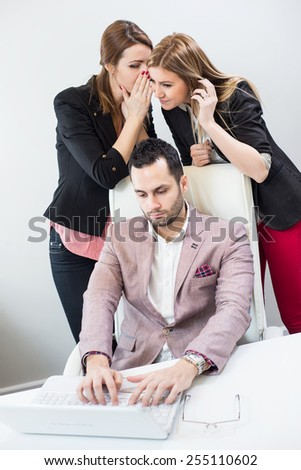 Two attractive young businesswomen gossip about a male co-worker. - stock photo