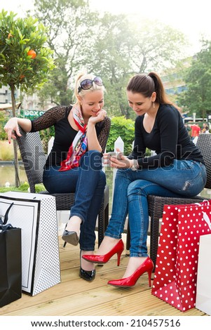 Two attractive young female friends enjoying a day out after successful shopping