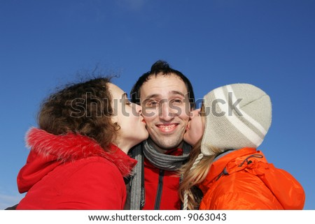 Two attractive young girl kissing guy