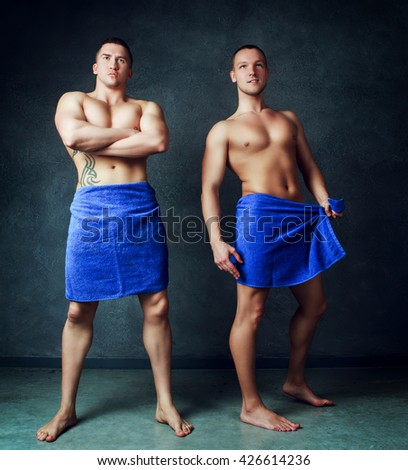 two attractive young men wearing towels after taking a shower, against dark studio background - stock photo