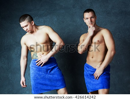 two attractive young men with towels on their hips after taking a shower, against studio background - stock photo