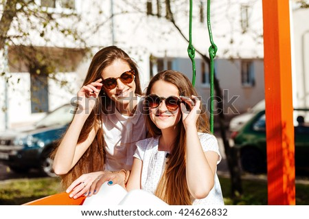 Two attractive young sisters with long beautiful hair. Girls in sunglasses. Walk through the city streets. Happy women  - stock photo