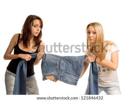 Two attractive young teenage women having a tug of war over a pair of denim jeans as each pulls on a leg while looking at the camera