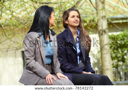two attractive young woman sits in the park and discuss about something, outdoor shoot - stock photo