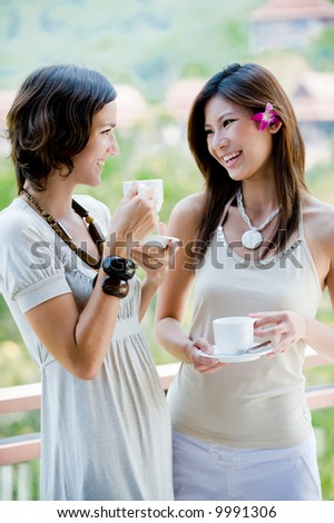 Two attractive young women catching up over coffee outside - stock photo