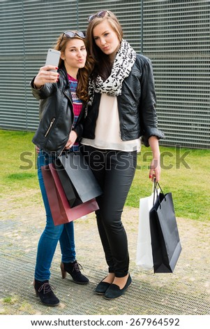 Two attractive young women making a selfie outside of the shopping mall carrying their bags - stock photo