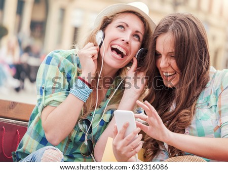 Two attractive young women resting on the bench after shopping and listening to music with a mobile phone. Consumerism, fashion, lifestyle concept