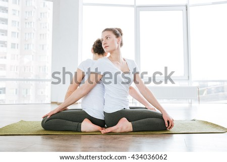 Two attractive young women sitting and doing stretching exercises in yoga studio - stock photo