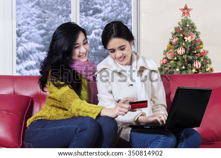 Two attractive young women using credit card and laptop computer for shopping online at home while wearing winter clothes with christmas tree background - stock photo