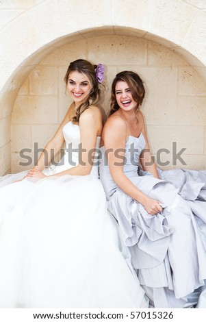 Two attractive young women wearing formal dresses are smiling and sitting back to back in an alcove. Vertical shot. - stock photo