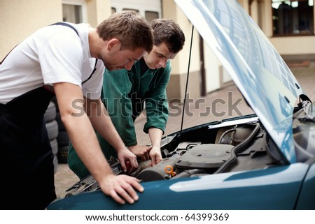 Two auto mechanics examining car with open hood. - stock photo