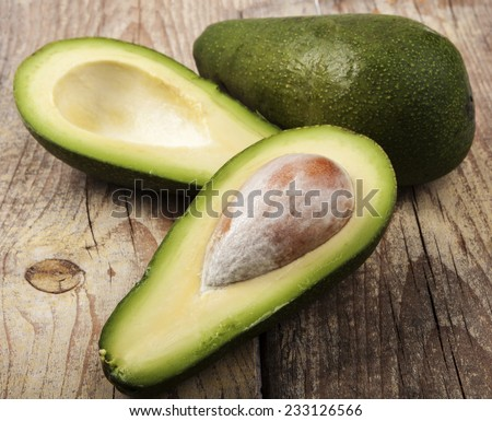 Two avocado one cut in half on old brown wood - stock photo