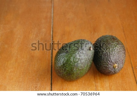 Two Avocados on an Old Wooden Table with Room for Text - stock photo